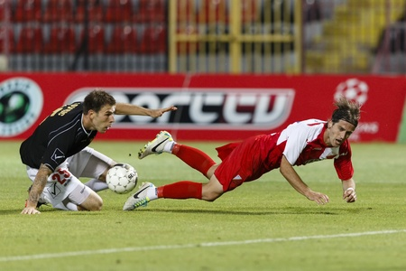 commits: BUDAPEST - July 25: Ivan Lovric of Honved (L) commits a foul against Stojan Vranjes of Vojvodina during Honved vs. Vojvodina UEFA Europa League football game at Bozsik Stadium on July 25, 2013 in Budapest, Hungary.