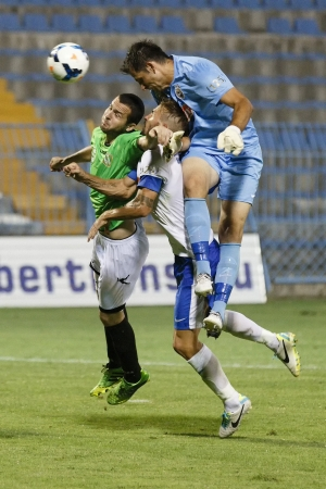 teammate: BUDAPEST - AUGUST 9: Goalkeeper Federico Groppioni of MTK (R) heads the ball after corner kick behind his teammate Andras Fejes and Bence Iszlai of Haladas (R) during MTK vs. Haladas OTP Bank League football match at Hidegkuti Stadium on August 9, 2013 in