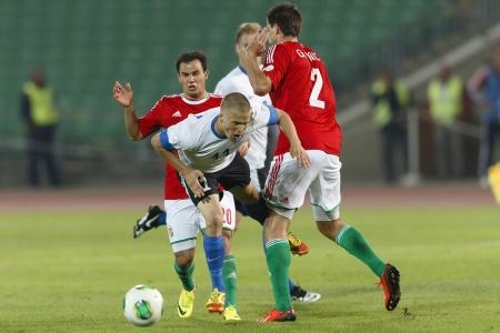 commits: BUDAPEST - SEPTEMBER 10: Hungarian Tamas Hajnal (L) commits a foul against Estonian Henrik Ojamaa during Hungary vs. Estonia World Cup qualifier match at Puskas Stadium on September 10, 2013 in Budapest, Hungary.