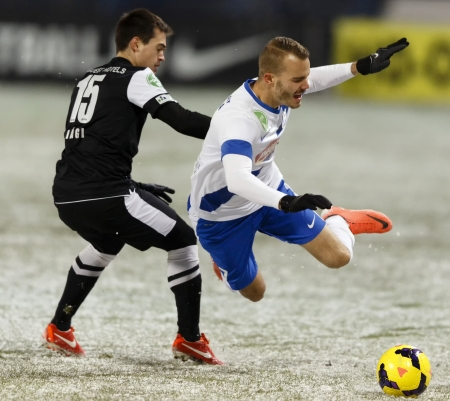 commits: BUDAPEST - DECEMBER 7: Andras Vagi of DVTK commits a foul against Zsolt Horvath of MTK (r)  during MTK vs. DVTK OTP Bank League match at Hidegkuti Stadium on December 7, 2013 in Budapest, Hungary.