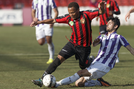 cameroonian: BUDAPEST, HUNGARY - MARCH 1, 2014: Jose Samper of Ujpest commits a foul against Thomas Job of Honved (l)  during Budapest Honved vs. Ujpest FC OTP Bank League football match at Bozsik Stadium on March 1, 2014 in Budapest, Hungary.  Editorial