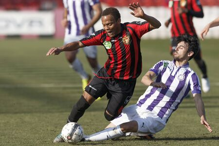 commits: BUDAPEST, HUNGARY - MARCH 1, 2014: Jose Samper of Ujpest commits a foul against Thomas Job of Honved (l)  during Budapest Honved vs. Ujpest FC OTP Bank League football match at Bozsik Stadium on March 1, 2014 in Budapest, Hungary.  Editorial