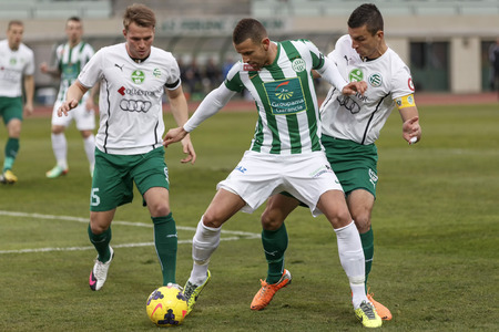 BUDAPEST, HUNGARY - MARCH 2, 2014: Attila Busai of Ferencvaros (m) between Daniel Volgyi (l) and Zoltan Liptak of Gyor during Ferencvaros vs. Gyori ETO OTP Bank League football match at Puskas Stadium on March 2, 2014 in Budapest, Hungary.
