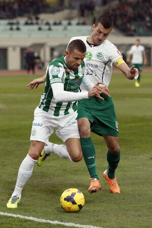 BUDAPEST, HUNGARY - MARCH 2, 2014: Attila Busai of Ferencvaros (l) is tackled by Zoltan Liptak of Gyor during Ferencvaros vs. Gyori ETO OTP Bank League football match at Puskas Stadium on March 2, 2014 in Budapest, Hungary.  Editorial