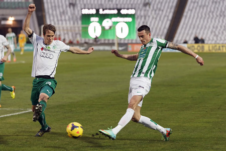 BUDAPEST, HUNGARY - MARCH 2, 2014: Julian Jenner of Ferencvaros (r) tries to cross the ball beside Michal Svec of Gyor during Ferencvaros vs. Gyori ETO OTP Bank League football match at Puskas Stadium on March 2, 2014 in Budapest, Hungary.