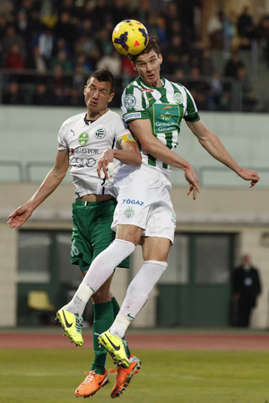 BUDAPEST, HUNGARY - MARCH 2, 2014: Mateo Pavlovic of Ferencvaros (r) heads on goal beside Zoltan Liptak of Gyor during Ferencvaros vs. Gyori ETO OTP Bank League football match at Puskas Stadium on March 2, 2014 in Budapest, Hungary.