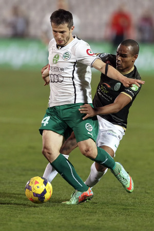 BUDAPEST, HUNGARY - MARCH 2, 2014: Leonardo Santiago of Ferencvaros (r) pulls back Gergely Rudolf of Gyor during Ferencvaros vs. Gyori ETO OTP Bank League football match at Puskas Stadium on March 2, 2014 in Budapest, Hungary.
