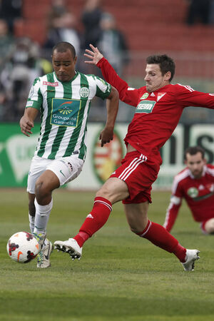 BUDAPEST, HUNGARY - MARCH 16, 2014: Laszlo Zsidai of DVSC tries to stop Leonardo Santiago of Ferencvaros (l)  during Ferencvaros vs. Debreceni VSC OTP Bank League football match at Puskas Stadium on March 16, 2014 in Budapest, Hungary.