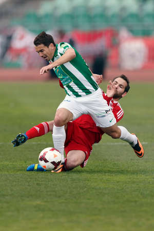 BUDAPEST, HUNGARY - MARCH 16, 2014: Andrei Ionescu of Ferencvaros (l) is tackled by Selim Bouadla of DVSC during Ferencvaros vs. Debreceni VSC OTP Bank League football match at Puskas Stadium on March 16, 2014 in Budapest, Hungary.