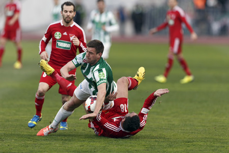 BUDAPEST, HUNGARY - MARCH 16, 2014: Daniel Bode of Ferencvaros (m) falls on Peter Mate of DVSC (r) - Selim Bouadla in the background - during Ferencvaros vs. Debreceni VSC OTP Bank League football match at Puskas Stadium on March 16, 2014 in Budapest, Hun