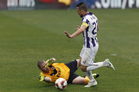 tripped: BUDAPEST, HUNGARY - MARCH 23, 2014: Peter Kabat of Ujpest (r) is tripped up by Nenad Rajic of DVTK during Ujpest vs. DVTK OTP Bank League football match at Szusza Stadium on March 23, 2014 in Budapest, Hungary.