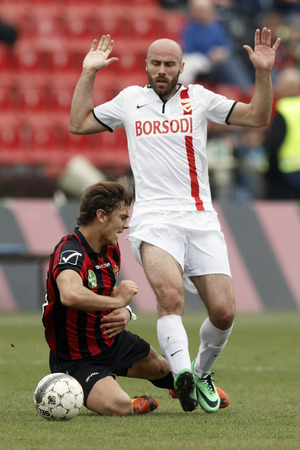 fails: BUDAPEST, HUNGARY - APRIL 5, 2014: Miroslav Grumic of DVTK fails Balint Vecsei of Honved (l) during Honved vs. DVTK OTP Bank League football match at Bozsik Stadium on April 5, 2014 in Budapest, Hungary.