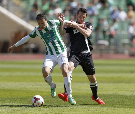 BUDAPEST, HUNGARY - MAY 10, 2014: Akos Elek (r) of Diosgyor tries to tackle Vladan Cukic of Ferencvaros during Ferencvaros vs. Diosgyori VTK OTP Bank League football match at Puskas Stadium on May 10, 2014 in Budapest, Hungary.