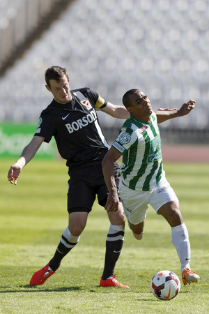 BUDAPEST, HUNGARY - MAY 10, 2014: Leonardo Santiago of Ferencvaros (l) is tripped up by Akos Elek of Diosgyor during Ferencvaros vs. Diosgyori VTK OTP Bank League football match at Puskas Stadium on May 10, 2014 in Budapest, Hungary.