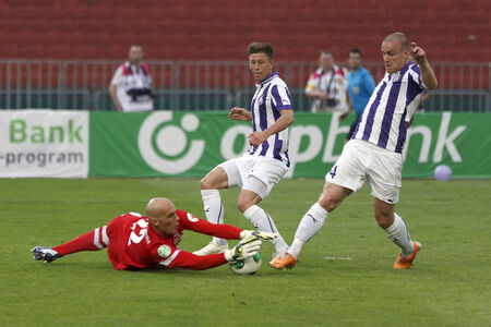 BUDAPEST, HUNGARY - MAY 25, 2014: Ivan Rados of DVTK saves the ball from Filip Stanisavljevic (r) and Krisztian Simon of Ujpest (m) during Ujpest vs. Diosgyori VTK Hungarian Cup final football match at Puskas Stadium on May 25, 2014 in Budapest, Hungary.