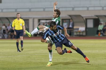 BUDAPEST, HUNGARY - JULY 10, 2014: Duel between Benjamin Lauth of FTC (l) and Filippo Scozzese of Sliema during Ferencvarosi TC vs. Sliema UEFA EL football match at Puskas Stadium on July 10, 2014 in Budapest, Hungary.