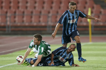 BUDAPEST, HUNGARY - JULY 10, 2014: Benjamin Lauth of FTC (l) tackled by Stefano Bianciardi and Marko Potezica (r) of Sliema during Ferencvarosi TC vs. Sliema UEFA EL football match at Puskas Stadium on July 10, 2014 in Budapest, Hungary.