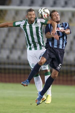 wanderers: BUDAPEST, HUNGARY - JULY 10, 2014: Air battle between Attila Busai of FTC (l) and Marko Potezica of Sliema during Ferencvarosi TC vs. Sliema UEFA EL football match at Puskas Stadium on July 10, 2014 in Budapest, Hungary.