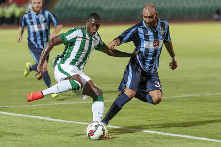 wanderers: BUDAPEST, HUNGARY - JULY 10, 2014: Somalia of FTC (l)dribbles next to Stefano Bianciardi of Sliema during Ferencvarosi TC vs. Sliema UEFA EL football match at Puskas Stadium on July 10, 2014 in Budapest, Hungary.  Editorial
