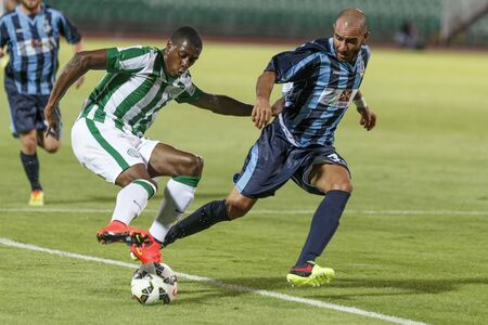 BUDAPEST, HUNGARY - JULY 10, 2014: Somalia of FTC (l)dribbles next to Stefano Bianciardi of Sliema during Ferencvarosi TC vs. Sliema UEFA EL football match at Puskas Stadium on July 10, 2014 in Budapest, Hungary.  Editorial