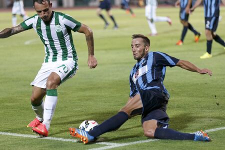 wanderers: BUDAPEST, HUNGARY - JULY 10, 2014: Roland Ugrai of FTC (l) tacked by Marko Potezica of Sliema during Ferencvarosi TC vs. Sliema UEFA EL football match at Puskas Stadium on July 10, 2014 in Budapest, Hungary.