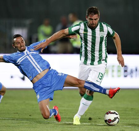 commits: BUDAPEST, HUNGARY - JULY 24, 2014: Marin Leovac of Rijeka commits a foul against Daniel Bode of FTC (r) during Ferencvarosi TC vs. HNK Rijeka UEFA EL football match at Puskas Stadium on July 24, 2014 in Budapest, Hungary.