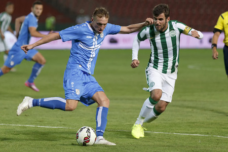 BUDAPEST, HUNGARY - JULY 24, 2014: Vedran Jugovic of Rijeka shots the ball from Gabor Gyomber of FTC (r) during Ferencvarosi TC vs. HNK Rijeka UEFA EL football match at Puskas Stadium on July 24, 2014 in Budapest, Hungary.