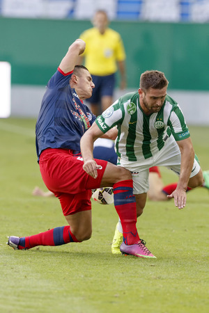 bode: BUDAPEST, HUNGARY - AUGUST 24, 2014: Daniel Bode of FTC (r) is fouled by Ferenc Fodor of Nyiregyhaza during Ferencvaros vs. Nyiregyhaza OTP Bank League football match at Groupama Arena on August 24, 2014 in Budapest, Hungary.