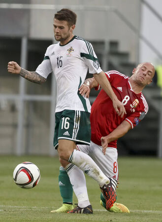 BUDAPEST, HUNGARY - SEPTEMBER 7, 2014: Hunagrian Jozsef Varga (r) is overtaken by Northern Irish Oliver Norwood during Hungary vs. Northern Ireland UEFA Euro 2016 qualifier football match at Groupama Arena on September 7, 2014 in Budapest, Hungary.