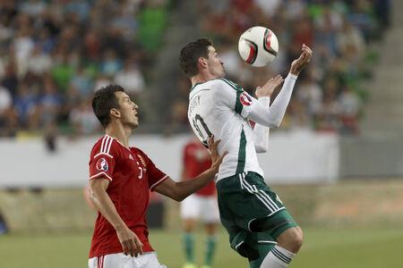 overtaken: BUDAPEST, HUNGARY - SEPTEMBER 7, 2014: Hunagrian Zoltan Liptak (l) is overtaken by Northern Irish Kyle Lafferty during Hungary vs. Northern Ireland UEFA Euro 2016 qualifier football match at Groupama Arena on September 7, 2014 in Budapest, Hungary.
