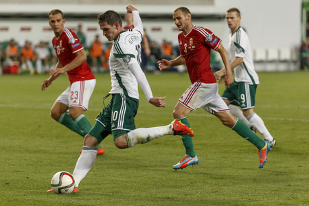 kyle: BUDAPEST, HUNGARY - SEPTEMBER 7, 2014: Hunagrian Roland Juhasz (l) and Vilmos Vanczak (r) watch the cross of Northern Irish Kyle Lafferty during Hungary vs. Northern Ireland UEFA Euro 2016 qualifier football match at Groupama Arena on September 7, 2014 in