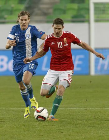 qualifier: BUDAPEST, HUNGARY - NOVEMBER 14, 2014: Finnish Markus Halsti tries to stop Hunagrian Zoltan Gera (r) during Hungary vs. Finland UEFA Euro 2016 qualifier football match in Groupama Arena on November 14, 2014 in Budapest, Hungary.