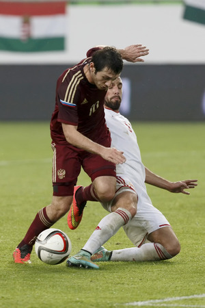 BUDAPEST, HUNGARY - NOVEMBER 18, 2014: Hunagrian Attila Fiola (r) tries to tackle Russian Alan Dzagoev during Hungary vs. Russia friendly football match in Groupama Arena on November 18, 2014 in Budapest, Hungary. Stok Fotoğraf - 33841579