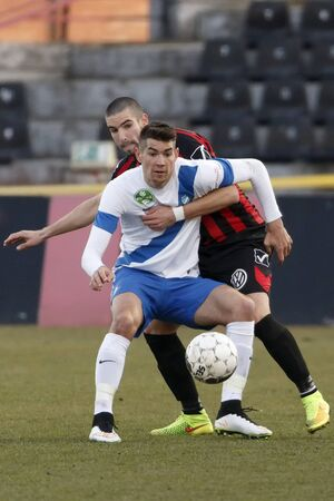 barnabas: BUDAPEST, HUNGARY - MARCH 8, 2015: Marko Vidovic of Honved (r) holds back Barnabas Bese of MTK during Honved vs. MTK OTP Bank League football match in Bozsik Stadium.