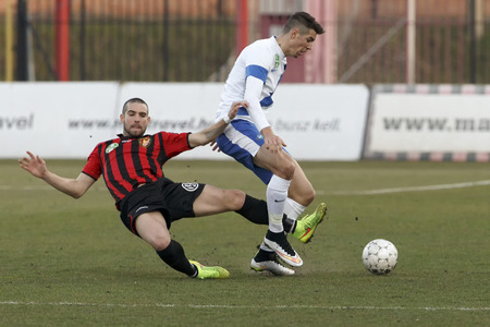 barnabas: BUDAPEST, HUNGARY - MARCH 8, 2015: Marko Vidovic of Honved (l) slides against Barnabas Bese of MTK during Honved vs. MTK OTP Bank League football match in Bozsik Stadium.