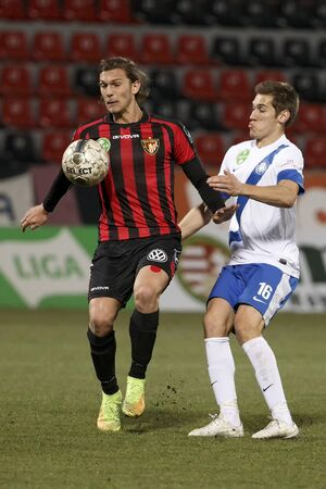 patrik: BUDAPEST, HUNGARY - MARCH 8, 2015: Patrik Hidi of Honved (l) is watched by Zsolt Poloskei of MTK during Honved vs. MTK OTP Bank League football match in Bozsik Stadium. Editorial