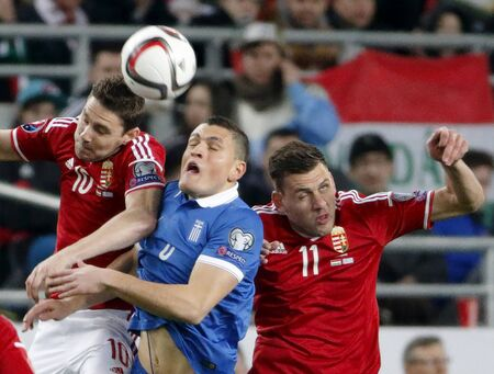 qualifier: BUDAPEST, HUNGARY - MARCH 29, 2015: Between Hungarian Zoltan Gera (l) and Adam Szalai (r) is the Greek Kyriakos Papadopoulos during Hungary vs. Greece UEFA Euro 2016 qualifier football match in Groupama Arena.