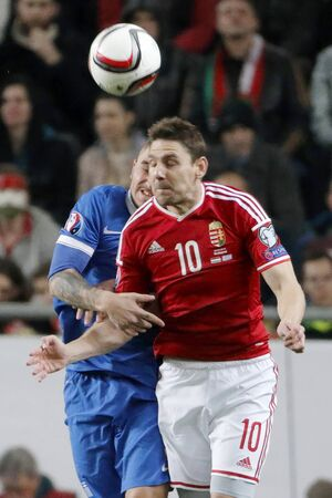qualifier: BUDAPEST, HUNGARY - MARCH 29, 2015: Air battle between Hungarian Zoltan Gera (r) and Greek Kostas Stafylidis during Hungary vs. Greece UEFA Euro 2016 qualifier football match in Groupama Arena. Editorial