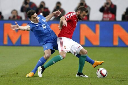 qualifier: BUDAPEST, HUNGARY - MARCH 29, 2015: Duel between Hungarian Attila Fiola (l) and Greek Lazaros Christodoulopoulos during Hungary vs. Greece UEFA Euro 2016 qualifier football match in Groupama Arena. Editorial
