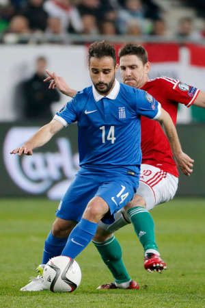 qualifier: BUDAPEST, HUNGARY - MARCH 29, 2015: Hungarian Zoltan Gera (r) tries to tackle Greek Giannis Fetfatzidis during Hungary vs. Greece UEFA Euro 2016 qualifier football match in Groupama Arena. Editorial