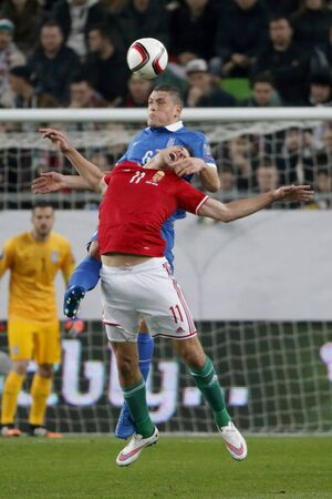 qualifier: BUDAPEST, HUNGARY - MARCH 29, 2015: Air battle between Hungarian Adam Szalai (11) and Greek Kyriakos Papadopoulos during Hungary vs. Greece UEFA Euro 2016 qualifier football match in Groupama Arena.