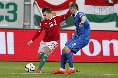 qualifier: BUDAPEST, HUNGARY - MARCH 29, 2015: Hungarian Zoltan Stieber (l) crosses the ball next to  Greek Kostas Stafylidis during Hungary vs. Greece UEFA Euro 2016 qualifier football match in Groupama Arena. Editorial