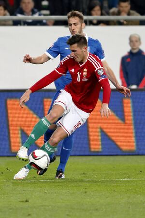 qualifier: BUDAPEST, HUNGARY - MARCH 29, 2015: Hungarian Adam Pinter (16) covers the ball from Greek Kostas Fortounis during Hungary vs. Greece UEFA Euro 2016 qualifier football match in Groupama Arena.