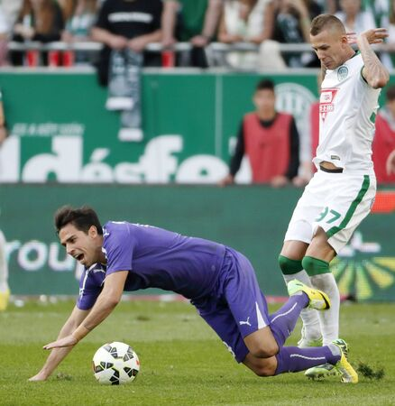 commits: BUDAPEST, HUNGARY - APRIL 12, 2015: Roland Varga of Ferencvaros (r) commits a foul against Nemanja Andric of Ujpest during Ferencvaros vs. Ujpest OTP Bank League football match in Groupama Arena. Editorial