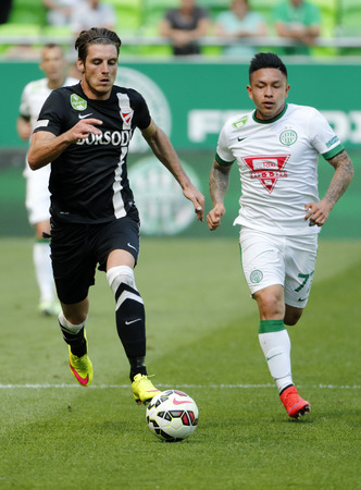 cristian: BUDAPEST, HUNGARY - APRIL 25, 2015: Cristian Ramirez of Ferencvaros (r) and Milan Nemeth of DVTK run after the ball during Ferencvaros vs. DVTK OTP Bank League football match in Groupama Arena.