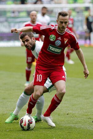 overtaken: BUDAPEST, HUNGARY - MAY 10, 2015: Gabor Gyomber of Ferencvaros (l) is overtaken by Rene Mihelic of DVSC during Ferencvaros vs. DVSC OTP Bank League football match in Groupama Arena.