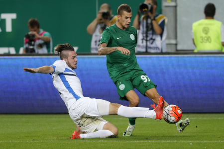 qualifier: BUDAPEST, HUNGARY - JULY 16, 2015: Roland Varga of Ferencvaros (r) is tackled by Kerim Memija of Zeljeznicar during Ferencvaros vs. Zeljeznicar UEFA EL qualifier football match in Groupama Arena.
