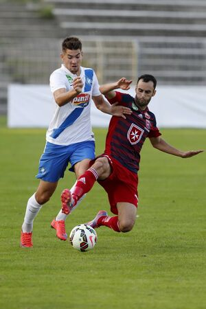 barnabas: BUDAPEST, HUNGARY - AUGUST 23, 2015: Barnabas Bese of MTK (l) is slided by Filipe Oliveira of Videoton during MTK vs. Videoton OTP Bank League football match in Illovszky Stadium.
