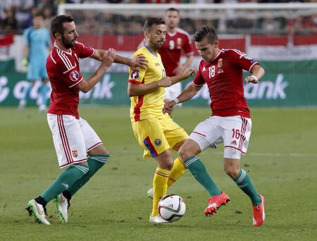 defence: BUDAPEST, HUNGARY - SEPTEMBER 4, 2015: Between Hungarian Attila Fiola (l) and Zoltan Stieber (18) watches the ball Romanian Lucian Sanmartean during Hungary vs. Romania UEFA Euro 2016 qualifier football match in Groupama Arena.