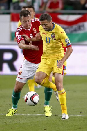 qualifier: BUDAPEST, HUNGARY - SEPTEMBER 4, 2015: Duel between Hungarian Daniel Tozser (l) and Romanian Lucian Sanmartean during Hungary vs. Romania UEFA Euro 2016 qualifier football match in Groupama Arena. Editorial